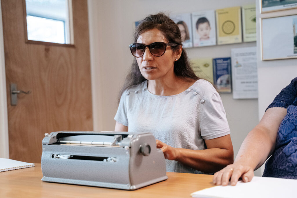 Woman learning on a Braille typing machine.