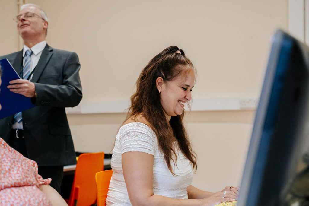 Woman sat at computer and smiling.