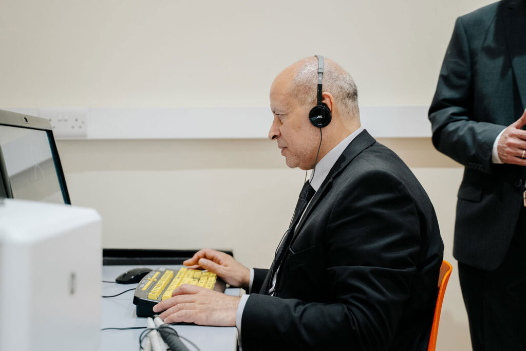 Visually impaired man sitting at computer wearing headphones.