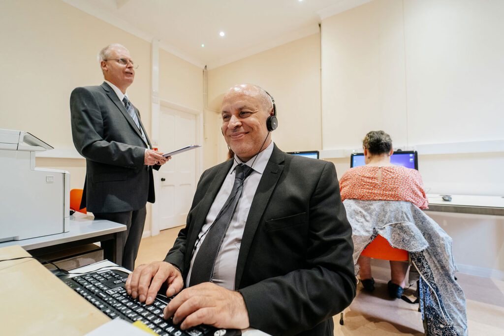 Visually impaired man sitting at a computer wearing headphones and smiling.