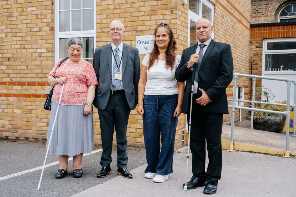 Visually impaired people standing outside a community centre.