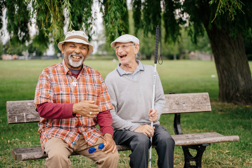 Volunteer sat on a bench with a visually impaired person, both laughing.