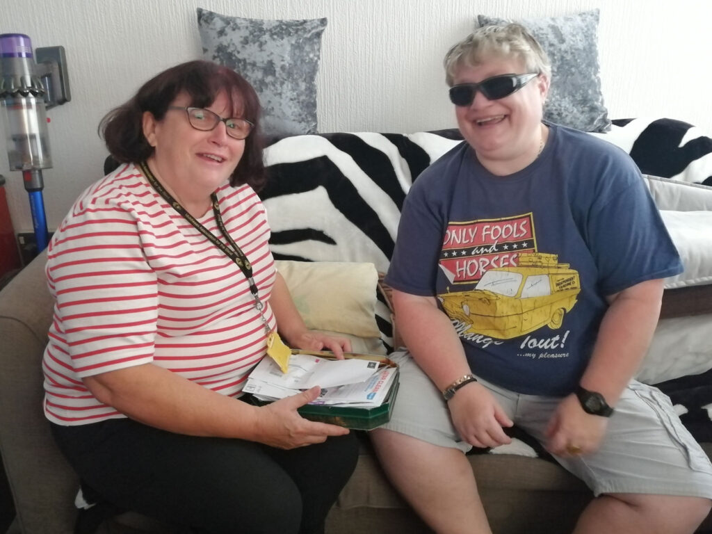 A volunteer sitting on a sofa with a visually impaired person.