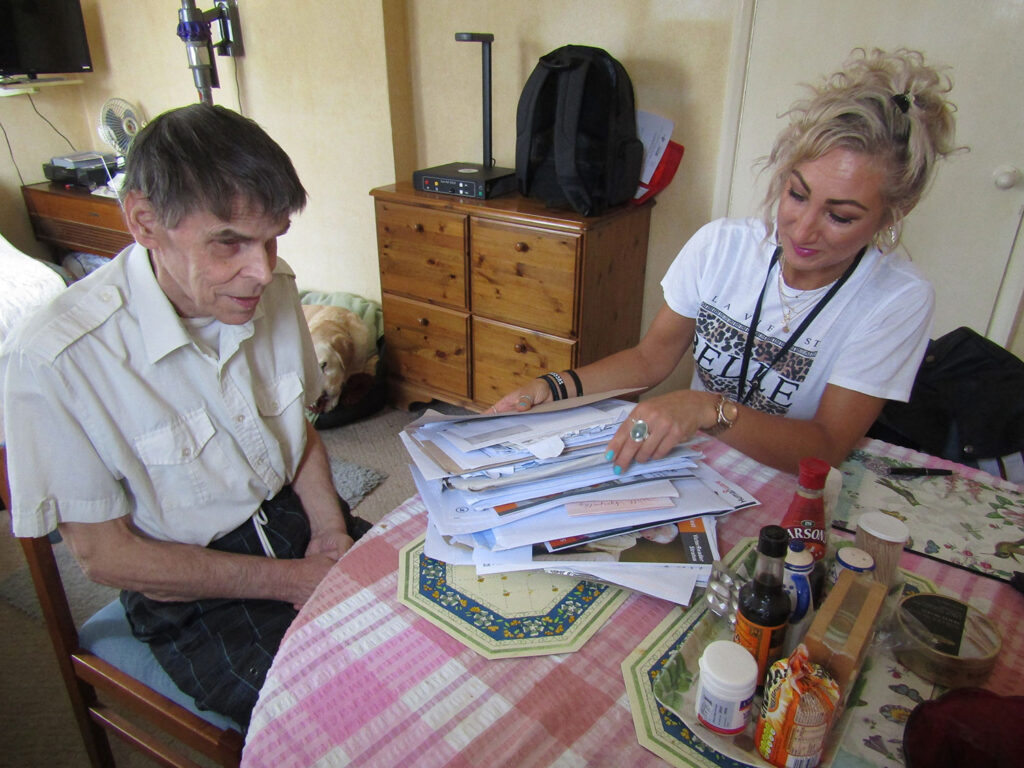 Volunteer helping a visually impaired person with their paperwork.